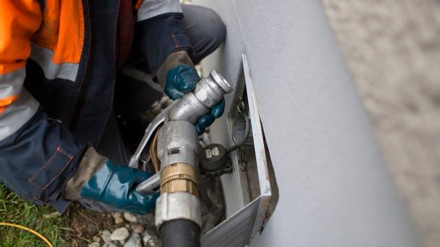 Ein Mann schraubt ein Rohr in eine Hauswand, durch das Heizöl fliessen soll.