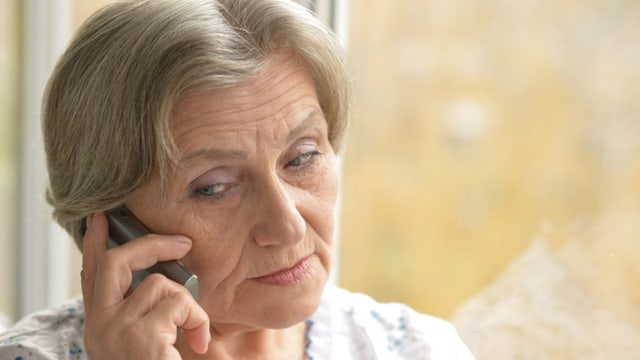 Eine ältere Dame steht am Fenster und telefoniert.