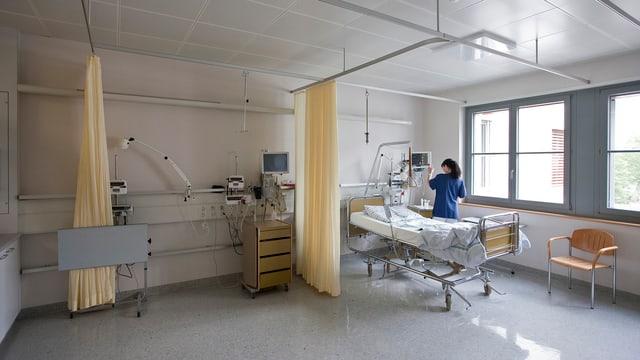 Symbolbild: Spitalzimmer mit Spitalbett am Fenster, eine Krankenschwester hantiert an Geräten.