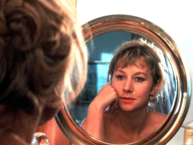 Helen Mirren schaut in einen goldenen Spiegel.