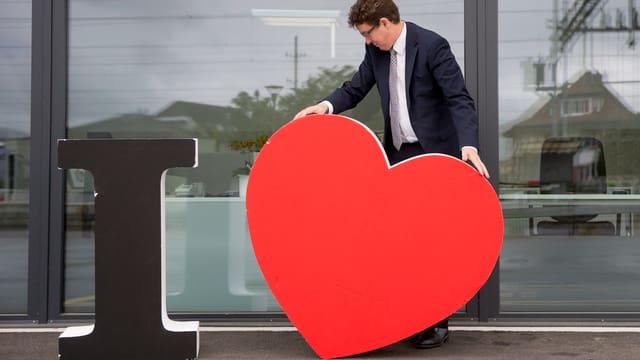 Rösti verschiebt ein grosses Deko-Herz, daneben steht ein grosses schwarzes «I».