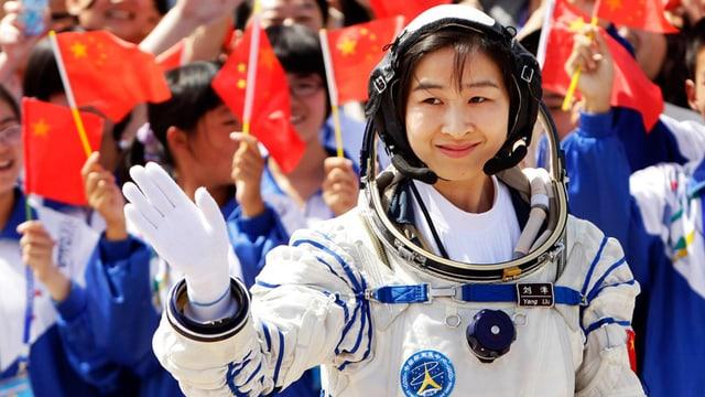 Liu Yang im Astronautenanzug winkt der jubelnden Menge zu.