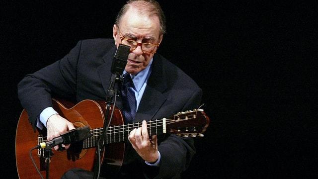 João Gilberto hät eine Gitarre in der Hand und singt ins Mikrofon, das vor ihm steht.