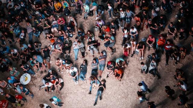 Dutzende Festivalbesucher sitzen am Boden