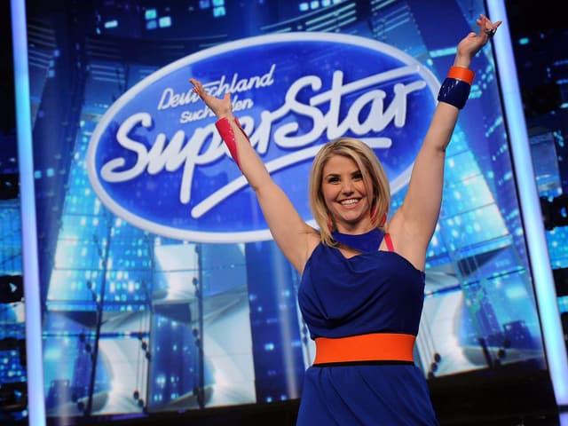 Beatrice Egli vor dem Logo zu «Deutschland sucht den Superstar» in feierlicher Pose.