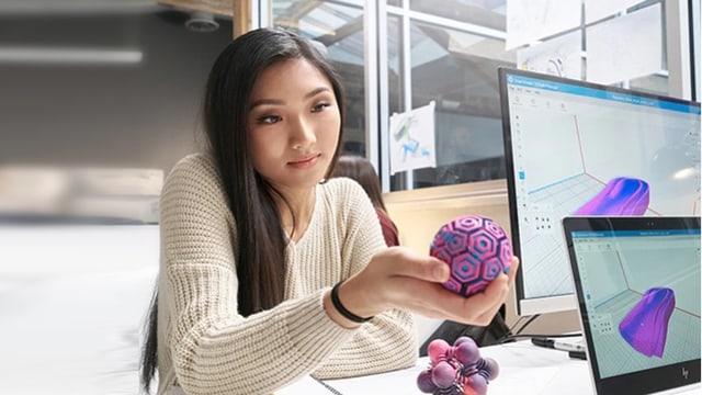 Frau hält bunten Gegenstand mit komplexer Oberfläche in den Händen.