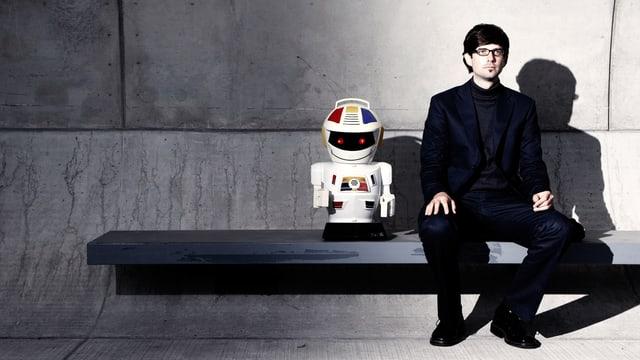 Mensch sitzt neben Roboter auf einer Bank.