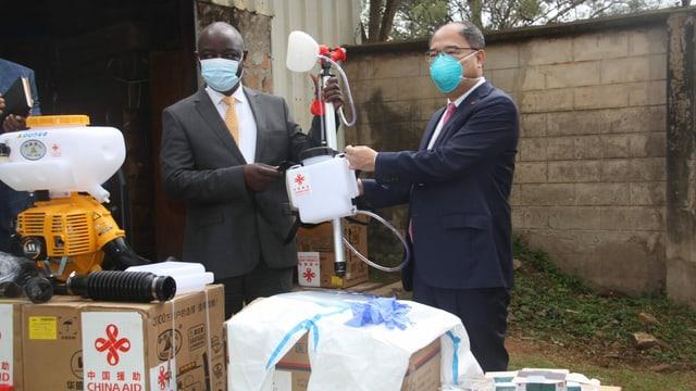 Personen halten Hilfsmaterial für die Coronakrise in der Hand.