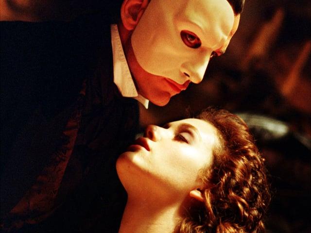 Mysteriöser Mann mit Maske beugt sich über leidenschaftlich blickende junge Frau.