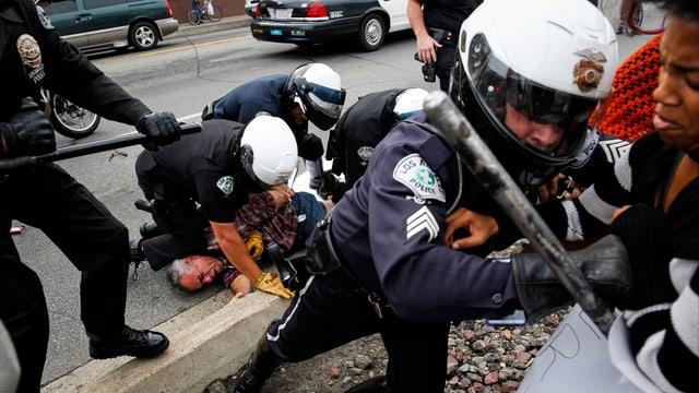 Polizisten halten Mann am Boden fest, ein weiterer Beamter geht gegen Umstehende vor.