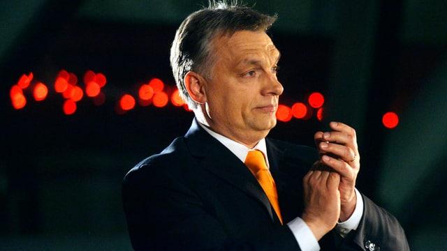 Ungarns Premier Viktor Orban klatscht vor dunklem Hintergrund in die Hände. (keystone)