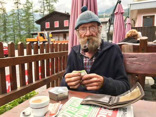 älterer Herr in Bosco/Gurin mit Blick Zeitung
