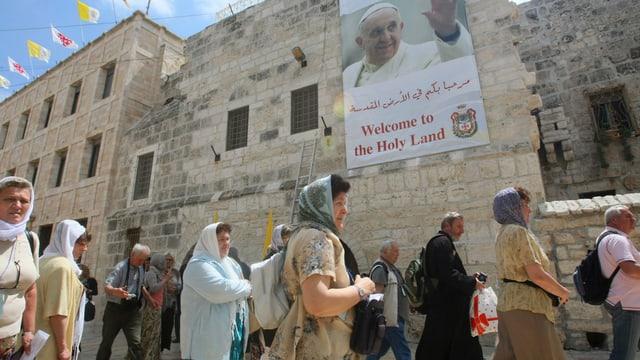 Touristen vor der Geburtskirche in Bethlehem, an der ein Poster mit dem Papst hängt