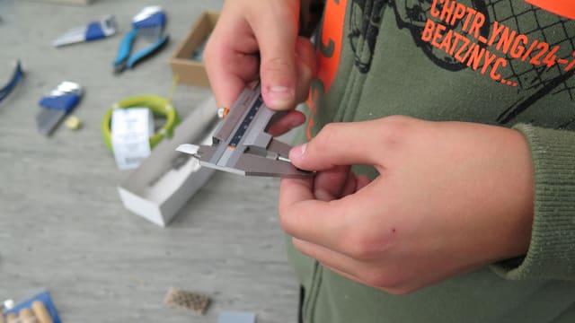 Schublehre misst breite eines Metallstifts.