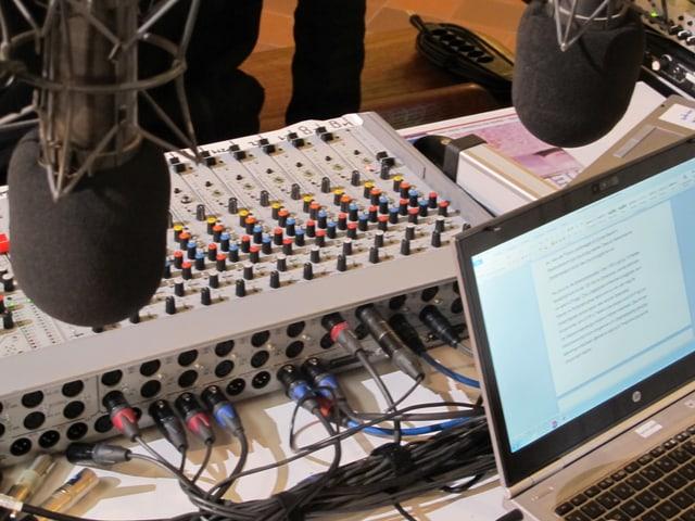 Ein Mischpult mit vielen Reglern, davor Mikrofone.