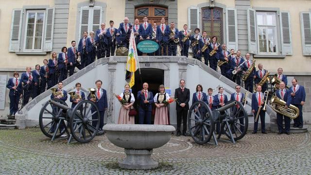Bild der Stadtmusik Grenchen - Mehrere Musiker stehen auf einer Treppe. Im Vordergrund stehen zwei Kanonen.