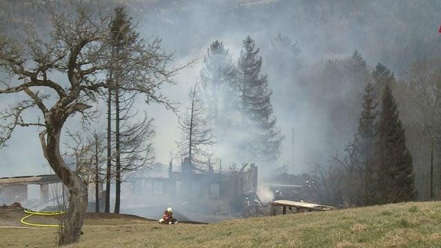 Bauernhof nach Brand in Rauch gehüllt.
