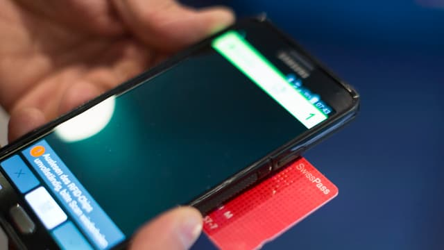 Handy und Swisspass, die ein Kontrolleur im Zug ansieht. man sieht nur Handy, Swisspass und Hände.