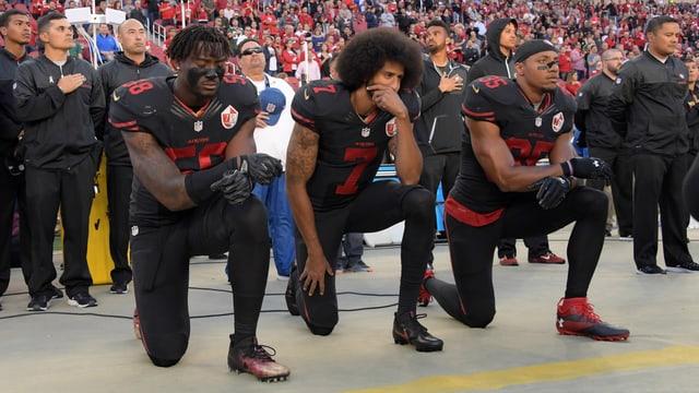 Die NFL-Spieler Eli Harold, Colin Kaepernick und Eric Reid von den San Francisco 49ers knien vor einem Spiel im Stadion.