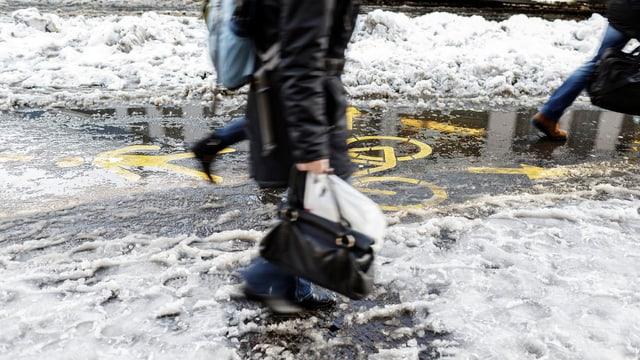 Eine Frau fährt mit dem Fahrrad über eine Strasse. Es schneit. Im Vodergrund ein Baum mit Schnee.