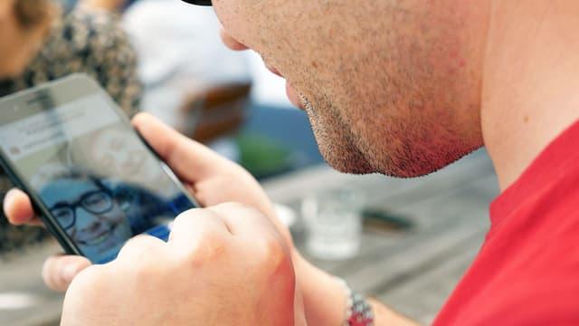Ein sehbehinderter Mann tippt auf dem Smartphone.