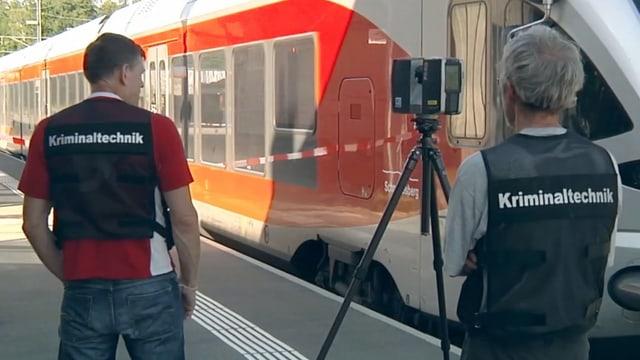 Kriminaltechniker stehen vor einem Zug.