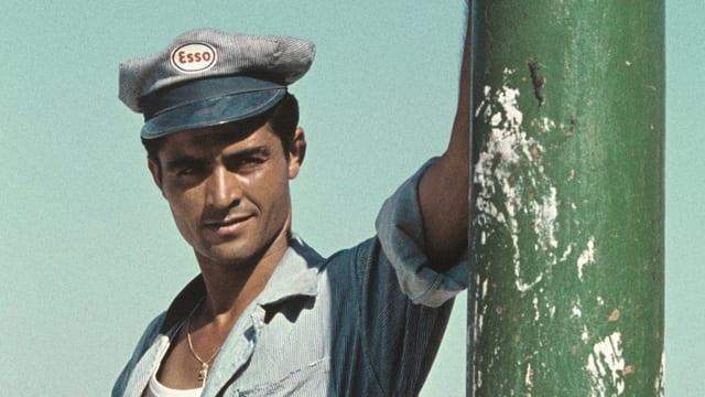 Mann mit Mütze lehnt an Metallstange
