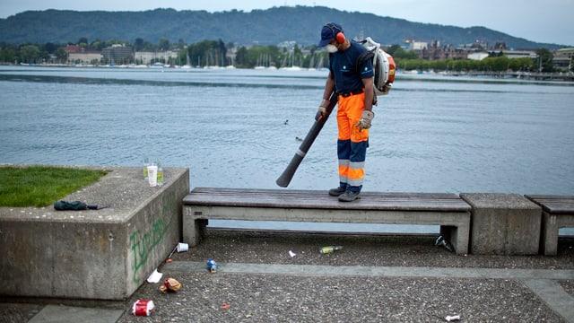 Ein Mann mit einem Laubbläser reinigt am frühen Morgen die Parkanlagen am Utoquai in Zuerich.