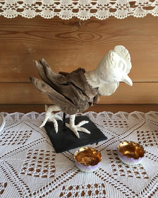 Ein Hahn aus Modelliermasse und Schwemmholz.