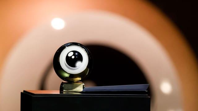 Auf einem Podest steht der Award in Form eines golden eingefassten Auges.
