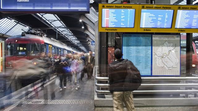 Ein Mann betrachtet am Bahnhof Zürich den Bildschirm mit den Zugsabfahrten