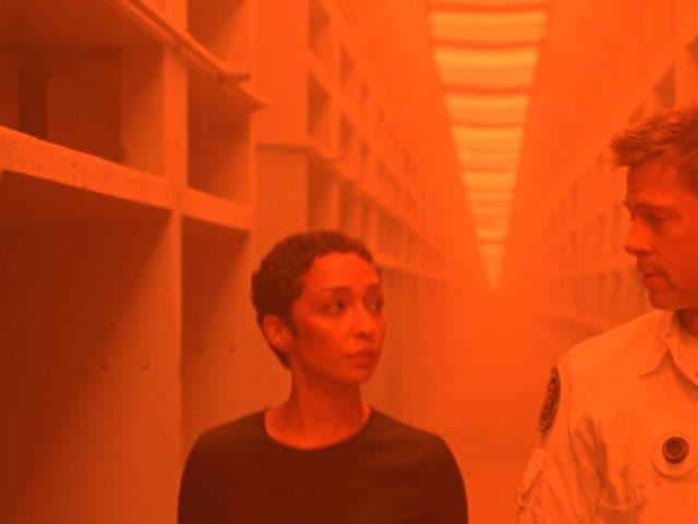 Brad Pitt und Ruth Negga in einem Gang, der orange beleuchtet ist.