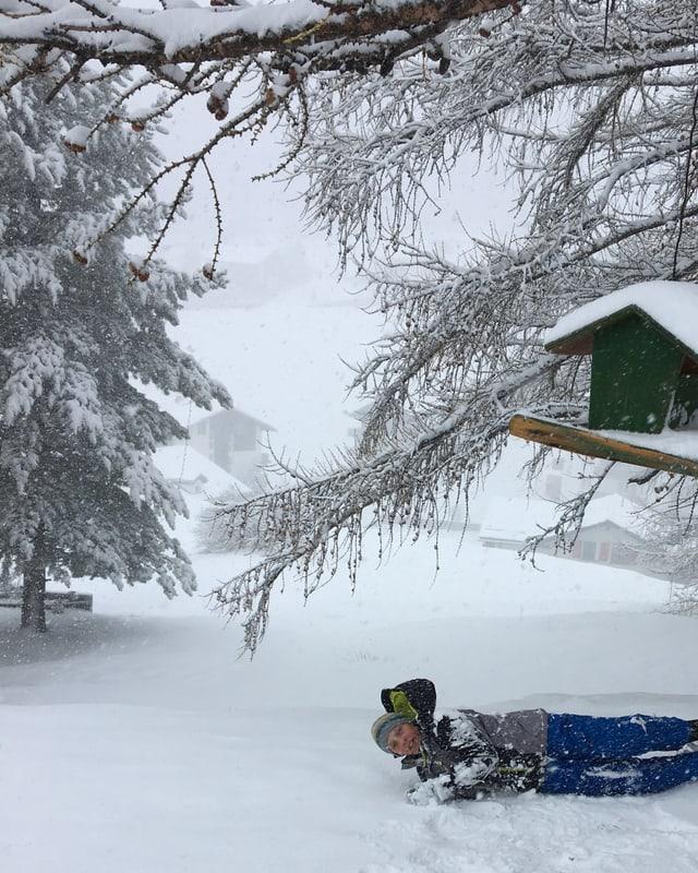 Ein Bub wälzt sich im Neuschnee.