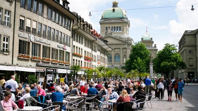 Numerusas persunas sesan en in café sin il 'Bärenplatz' a Berna.