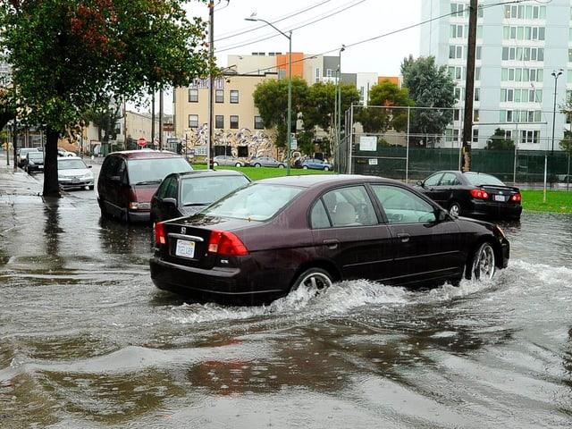 Ein Auto fährt auf überschwemmte Strassen.