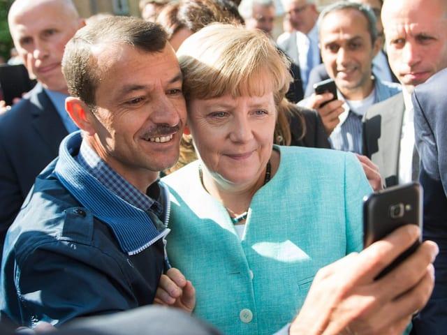 Bundeskanzlerin Angela Merkel macht ein Selfie mit einem Flüchtling.