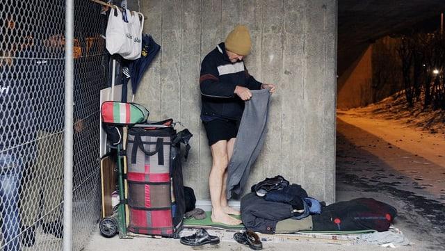 Ein obdachloser Mann wechselt die Kleiner.