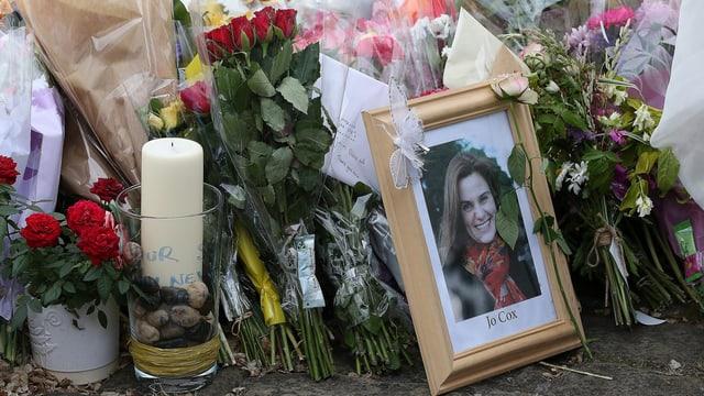 Niedergelegte Blumen und ein Foto von Jo Cox.