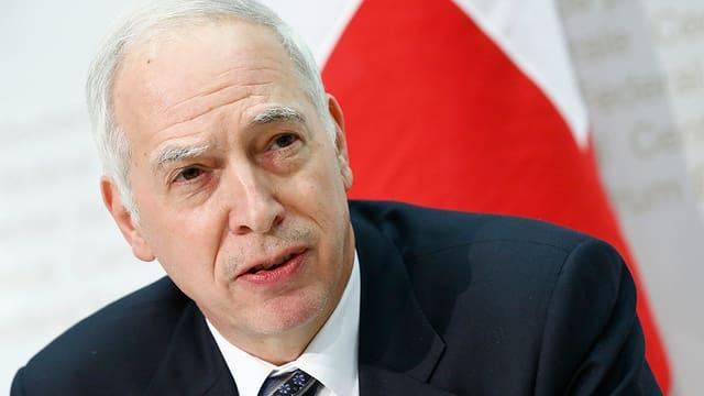 Botschafter Jacques de Watteville sitzt vor Schweizer Fahne
