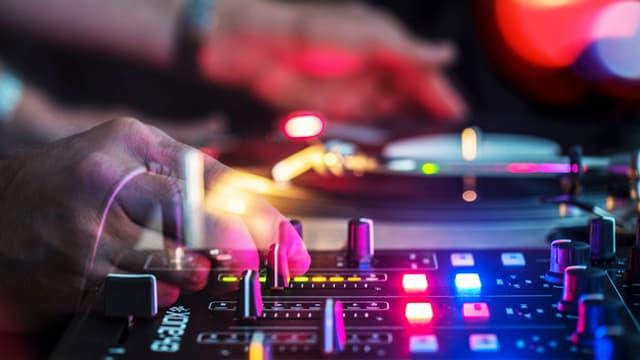 Hände an den Reglern eines DJ-Pults