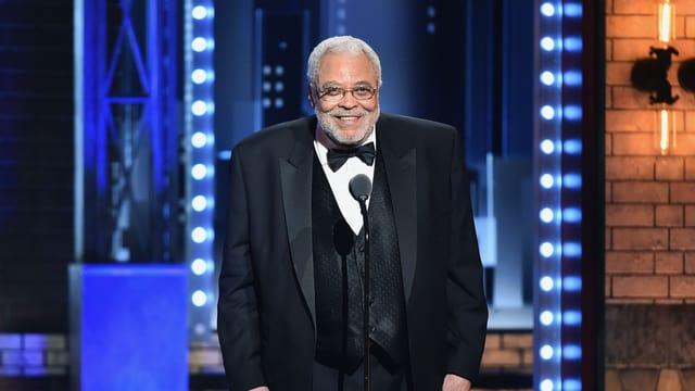 Ein breit gebauter Mann mit Anzug und Brille steht auf einer Bühne und lächelt.