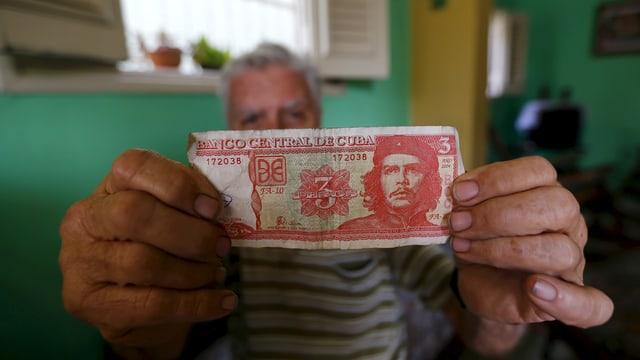 Ein Mann zeigt eine Drei-Peso-Note mit dem Konterfei Che Guevaras.
