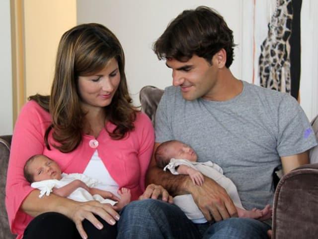 Charlene Riva und Myla Rose als Säuglinge in den Armen von Mirka und Roger Federer, die auf einem Sofa sitzen.