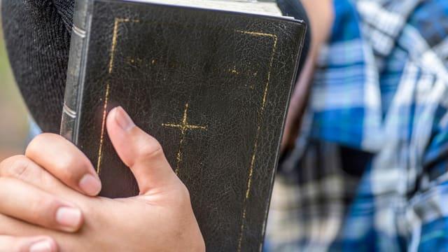Ein Mann, der seinen Kopf nach unten hält, hat seine Hände auf einer schwarze Bibel.