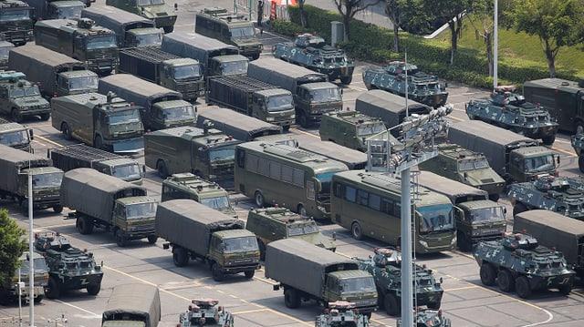 Dutzende geparkte Miltiärfahrzeuge, aus der Ferne fotografiert.