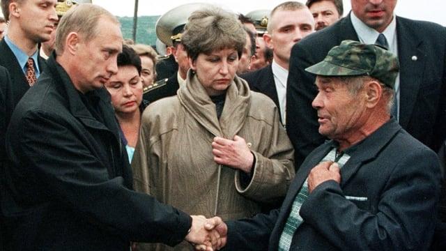 Putin schüttelt Mann die Hand.