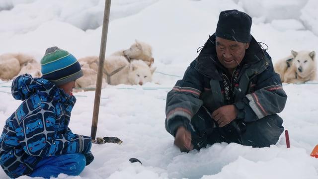 Auf dem Bild ist der kleine Junge Asser mit seinem Grossvater beim Eislochfischen zu sehen.