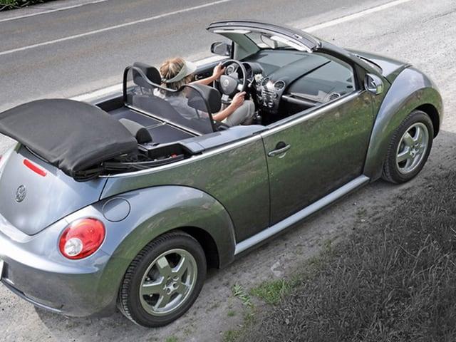 Ein hellgrauer VW-Käfer steht mitsamt Fahrerin darein, am Strassenrand.