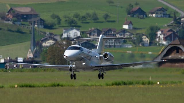Ein Kleinflugzeug startet auf einem Regionalflugplatz - im Hintergrund Häuser und Wiesen.
