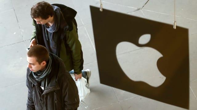 Personen gehen an einem Apple-Logo vorbei.
